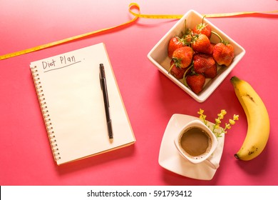 Diet plan book with pen on the pink background with fresh strawberry, banana and coffee