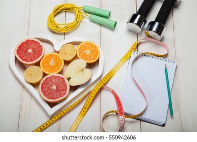 diet plan, dumbbells and centimeter on a white background