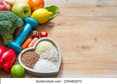 Diet plan and healthy lifestyle concept with vegetarian food in heart and gym dumbbell