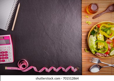 Diet plan, tape measure, calculator for Count calories,  salad healthy food on black stone background. Weight loss. Copy space.