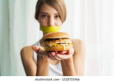 Diet. Portrait woman wants to eat a Burger but stuck skochem mouth, the concept of diet, junk food, willpower in nutrition