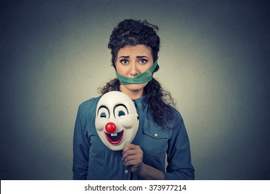 Diet restriction and stress concept. Portrait of young sad woman with clown mask and  measuring tape around her mouth isolated on gray wall background. Unhappy face expression emotion
