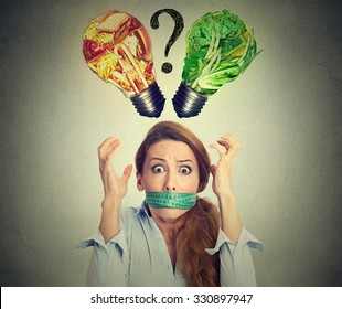Diet restriction stress concept. Young frustrated woman with a measuring tape around her mouth junk food and green vegetables shaped as light bulb above head. Face expression. Right nutrition choice