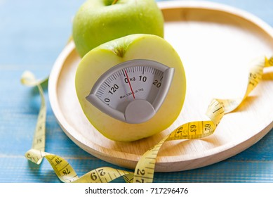 Diet slimming. Green apple with weight scale and measuring tape for the healthy. Diet and Healthy Concept.