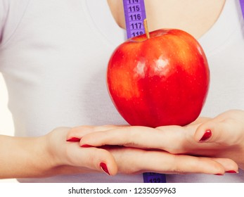 Diet and slimming, healthy food, fruits concept. Woman hands holding big red apple