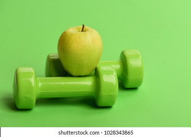 Diet and sport regime concept. Apple fruit near lightweight barbells, close up. Sports and healthy regime symbols. Dumbbells in bright green color and juicy fruit on top, green background