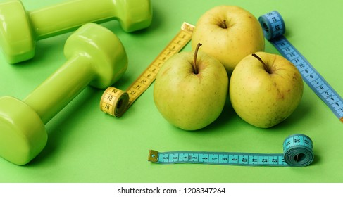 Diet and sport regime concept. Apples near dumbbells and measuring tapes trio on green background, close up. Sports and health symbols. Pattern made of apple fruits near barbells and tape measure