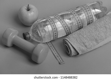 Diet and sport regime concept. Dumbbell in bright green color, water bottle, measure tape, towel and fruit on green background. Sports regime equipment. Barbell made of plastic by juicy green apple.