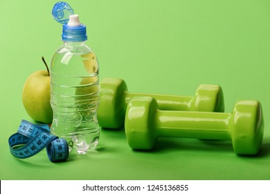 Diet and sport regime concept. Dumbbells in green color, water bottle, measure tape and fruit on green background. Barbells near juicy apple and blue tape. Sports and healthy regime equipment