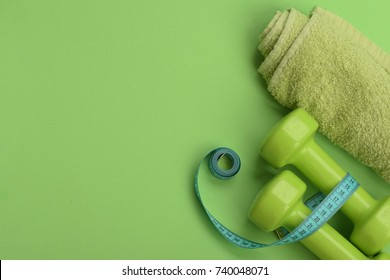 Diet and sport regime concept. Dumbbells in green color, twisted measure tape and towel on green background. Healthy lifestyle symbols. Tape measure in cyan color near lightweight barbells, copy space