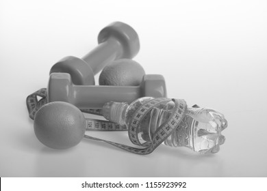 Diet and sport regime concept. Sports and healthy regime equipment. Dumbbells in bright green color, water bottle, measure tape and fruit on white background. Barbells made of plastic by juicy oranges
