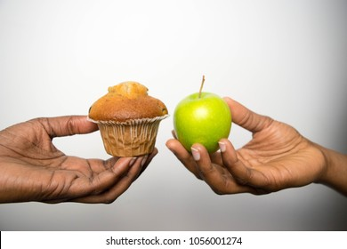 Diet struggle and deciding on nutrition choices dilemma between healthy good fresh fruit vegetables or cholesterol rich fast food competing what to eat hands cake green apple choosing African American