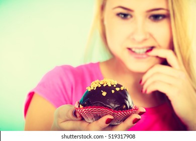 Diet, sweets, food concept. Cute blonde attractive woman thinking about eating delicious chocolate cupcake