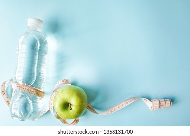 Diet symbol flat lay one meter ribbon and green apple and a bottle of water. blue background with copy space. health sport concept