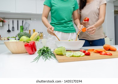 Diet. two young pretty woman in green shirt standing and preparing the vegetables salad in bowl for good healthy in modern kitchen at home, healthy lifestyle, cooking, healthy food and dieting concept