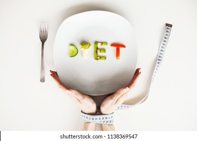 Diet or weight control concept. Centimeter tape and fork on a white background with a place for inserting text. concept of health, weight loss, diet, proper nutrition.