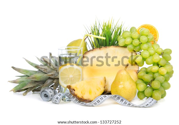 Diet weight loss breakfast concept with tape measure organic green grapes, orange juice, glass of lemon water juice, pineapple, pears on a white background