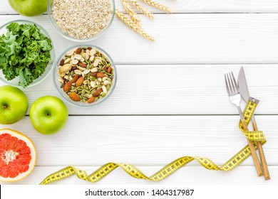 Diet for weight loss concept with measuring tape, greenary and oat on white background top view copy space