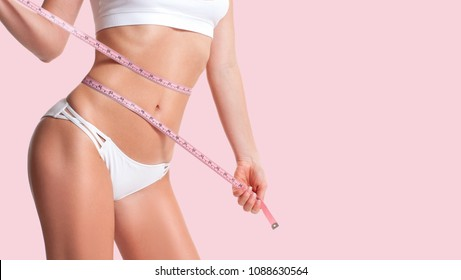 Diet and weight loss concept, perfect body. Beautiful woman measuring her waist with a measure tape on pink background