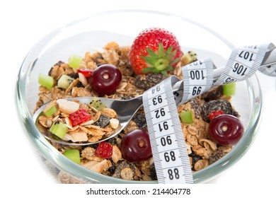 Diet weight loss concept tape measure spoon muesli cereals bowl almond, pine nuts, walnut, raisins, oat and wheat flakes, fresh fruits kiwi, strawberry pieces pomegranate seeds