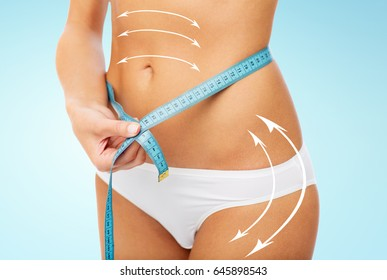 diet, weight loss and people concept - close up of woman body with measure tape around waist over blue background