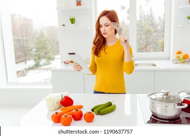 Diet, weight loss, slimming concept. Puzzled, questions lady look at screen of gadget ready prepare breakfast with tomato, cucumber, pepper, cabbage, carrots on the table in modern comfort interior