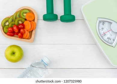Diet and weight loss for women healthy care with  weight scale and fitness equipment,fresh water and vitamins fruit healthy, apple, banana, carrot white wooden background top view.  Healthy Concept.