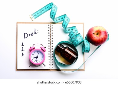 Diet and weight management concept: notebook with written note, pink alarm clock lying on it near glass bottle with pills and red apple tied with measuring tape, isolated on white background, top view