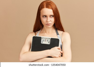 Diet and weight, young frustrated woman, looking aside, feeling unhealthy, embracing mechanical scales, being displeased by health problems and skin condition. Anorexia and underweight concept