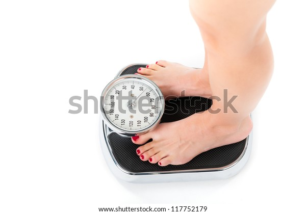 Diet and weight, young woman standing on a scale, only feet to be seen