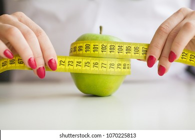 Diet. Woman holding a green apple and measuring