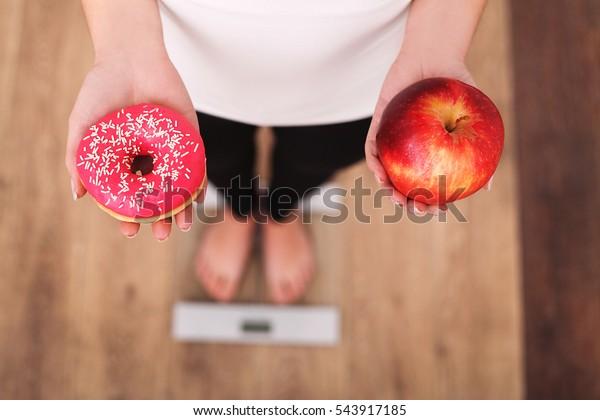 ダイエット。体重計で体重を測る女性で、ドーナツとリンゴを持つ。甘い物は不健康なジャンクフードだ。ダイエット健康食生活減量。肥満。トップビュー