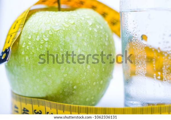 Diet.A apple with water and measuring tape on a white background