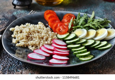 dietary  bowl salad with kinoa - tomatoes, radish, cucumbers, onions, arugula, grains kinoa, boiled egg. Fresh vitamin salad.