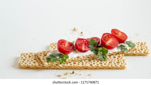 Dietary bread with tomato and greens on a white background