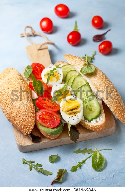 Dietary breakfast. Bun with cottage cheese, with tomato, cucumber, boiled egg, greens on a blue background