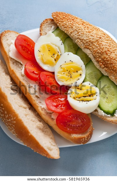 Dietary breakfast. Bun with cottage cheese, with tomato, cucumber, boiled egg on a blue background