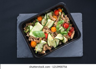 Dietary catering. Pasta salad with zucchini and tomatoes served on a black plate.