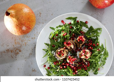 Dietary dish with eggplant. Eggplant roulades with cheese served with pomegranate on rocket lettuce.