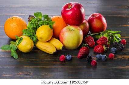dietary food fresh fruit and berries on a wooden table. healthy products apples, citrus fruits, berries. on dark background apples, bananas, oranges, mint, berries