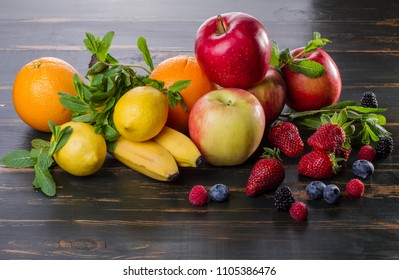 dietary food fresh fruit and berries on a wooden table. healthy products apples, citrus fruits, berries. on dark background bananas, oranges, mint, berries