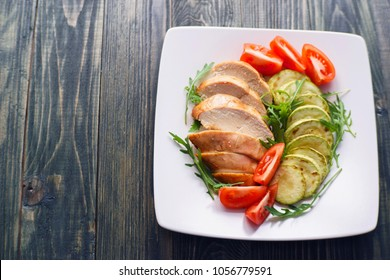Dietary food, proteins, healthy low-calorie eating concept. Baked chicken breasts with zucchini, tomatoes and arugula flat lay with copy space. Healthy meals background, diet concept