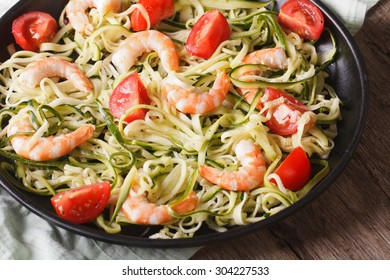 Dietary food: zucchini pasta with shrimp and tomato on a plate close-up. horizontal