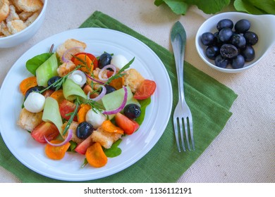 Dietary salad of cucumbers, tomatoes, carrots, roasted piece of bread, marinated mozzarella ball, black olives and red onions with olive oil in a plate on a fabrick background. Healthy food.