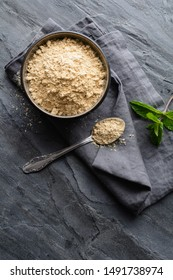 Dietary supplement, Maca root powder in a bowl and spoon on stone background with copy space