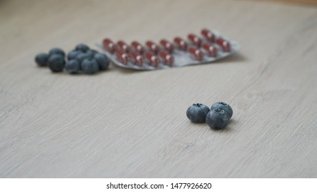 Dietary supplement - tablets for healthy eyes on a gray juicy background. A few berries in the center, pills in the background.