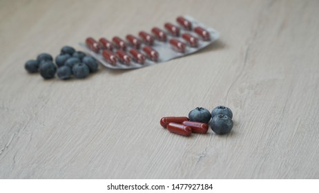 Dietary supplement - tablets for healthy eyes on a gray juicy background. Several berries and pills in the center, several berries and pills in the background.