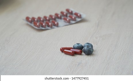 Dietary supplement - tablets for healthy eyes on a gray juicy background. Several berries and pills in the center, pills in the background.