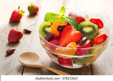 Diet-Fresh tasty mix fruit salad in the bowl on the wooden table, healthy breakfast, weight loss concept