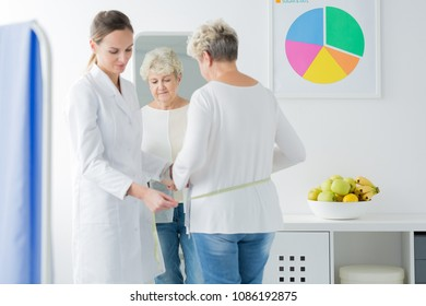 A dietician measuring a woman during a follow-up appointment